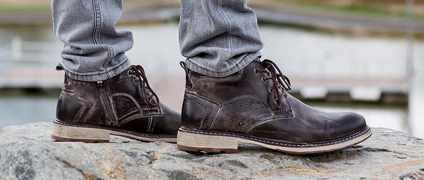 Close up of mens shoes on a rock wearing dark brown distressed leather Hypnos boot with light soles wearing grey denim