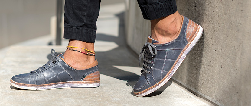 Close up of Navy and Tan leather Mens Milford sneakers with one foot against a concrete wall